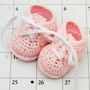 Pink baby booties on a calendar background, baby due date