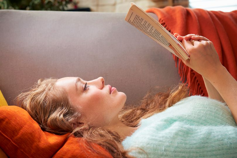 Young-woman-lying-on-sofa-reading