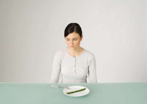 PROD-Young-woman-sitting-in-front-of-plate-with-single-asparagus-looking-away