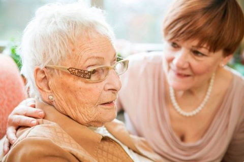 portrait-of-senior-woman-with-alzheimers-disease-with-her-adult-daughter-watching-in-the-background