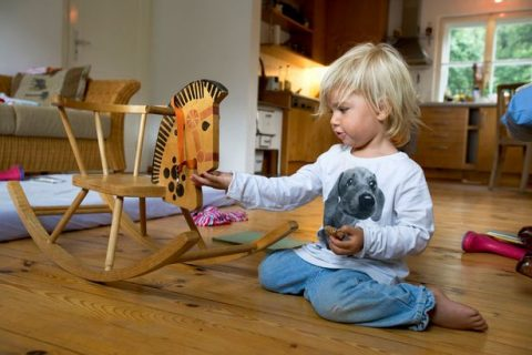 Girl-2-years-playing-with-rocking-horse-Berg-Bavaria-Germany